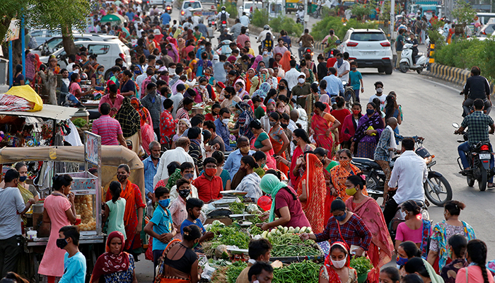 People shop at a crowded roadside vegetable market after authorities eased coronavirus restrictions, following a drop in COVID-19 cases in Ahmedabad, India, June 15, 2021. — Reuters/File