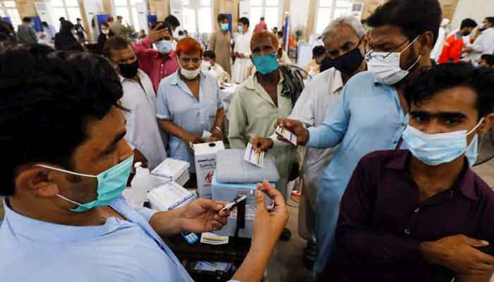 Residents with their registration cards gather at a counter to receive a dose of a COVID-19 vaccine, at a vaccination centre in Karachi, June 9, 2021. — Reuters/Akhtar Soomro