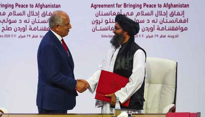 US special envoy Zalmay Khalilzad shakes hands with the head of the Talibans political office, Mullah Abdul Ghani Baradar, ahead of a peace conference in Doha, in this 2020 Reuters file photo.