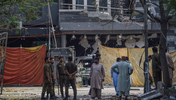 Police and locals stand near the site of an explosion in Lahore on June 24, 2021, a day after a car bomb killed three people in Pakistan´s eastern megacity. — AFP/File