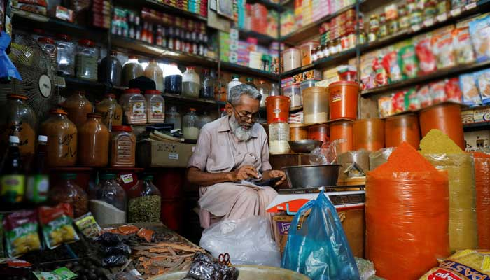 A shopkeeper uses a calculator while selling spices and grocery items along a shop in Karachi, Pakistan June 11, 2021. -REUTERS