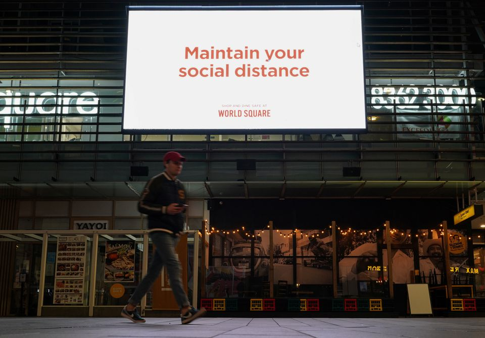 A man walks under a public health message about social distancing displayed at a shopping plaza in the city centre during a lockdown to curb the spread of a coronavirus disease (COVID-19) outbreak in Sydney, Australia, July 6, 2021. Photo: Reuters