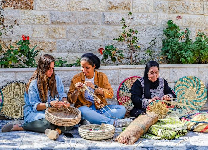 During their trip to Kifl Haris in Salfit, Umm Samer teaches travel bloggers Malak Hassan and Bisan Alhajhasan how to make trays weaved of wheat straws. Photo: Courtesy Ahlan Palestine
