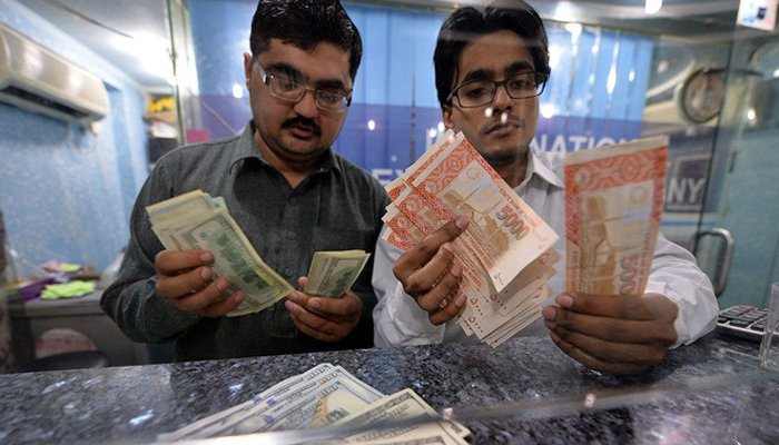 In this file photo, Money dealers count Pakistani rupees, right, and US dollars at a currency exchange in Islamabad on March 12, 2014. — AFP/File