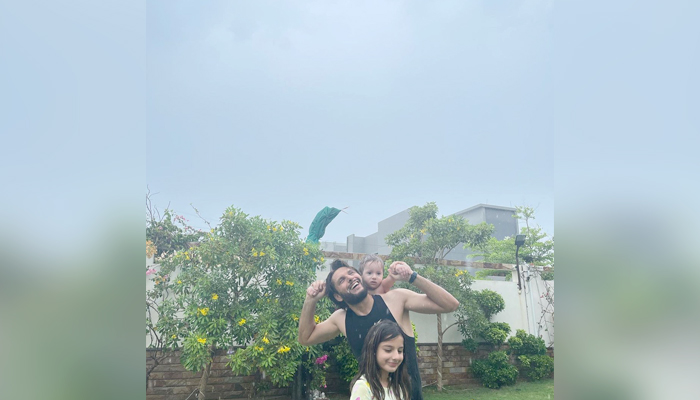 Shahid Afridi can be seen enjoying the first spell of monsoon rains with his daughters in Karachi, on July 12, 2021. — Instagram.