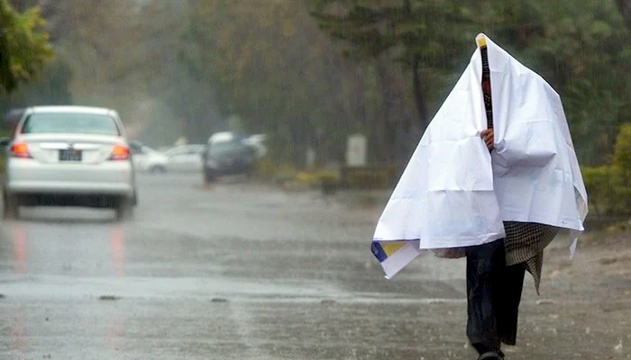 A man walking down the road and covering himself during rain. — AFP/File
