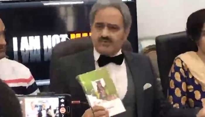 Clad in a tuxedo, Kashif Mirza speaks at a news conference in Lahore, clutching the book I am not Malala in his hand.