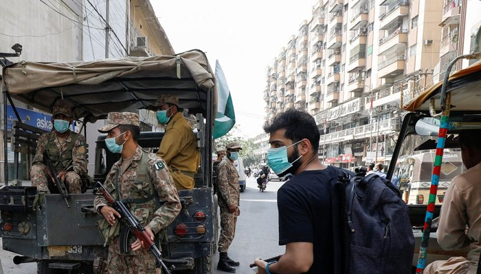 A resident wearing a protective mask walks past Pakistan Army soldiers on patrol to enforce coronavirus disease (COVID-19) safety protocols in Karachi, Pakistan April 28, 2021. — Reuters/File