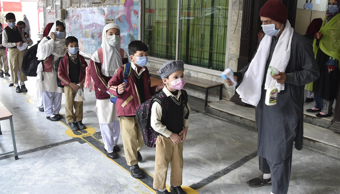 Student wear face masks as they arrive at their school at Peshawars Gulbhar colony, on February 1, 2021. — INP/File