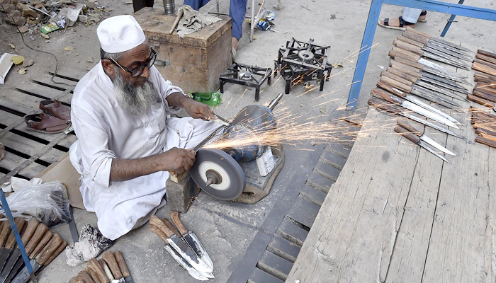 A blacksmith can be seen busy sharping knives to be used in slaughtering sacrificial animals in Peshawar, on July 11, 2021. — INP/File