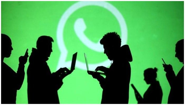 Silhouettes of mobile phone and laptop users are seen next to a screen projection of the WhatsApp logo, March 18, 2018. — Reuters/File