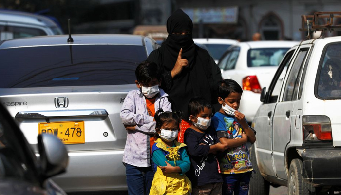 Children wear protective masks as they wait with their mother to cross the road, as the outbreak of the coronavirus disease (COVID-19) continues in Karachi, Pakistan. Picture taken January 15, 2021. Photo: Reuters