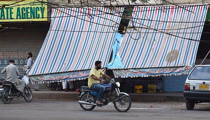 A commuter, wearing a mask to protect him against coronavirus, rides a bike in Karachi. — Geo.tv/Haseem uz Zaman/file