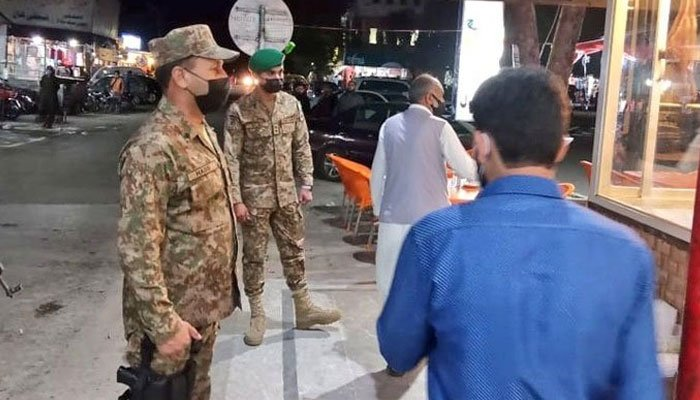 A file photo of Pakistan Army personnel helping people implement COVID-19 SOPs.