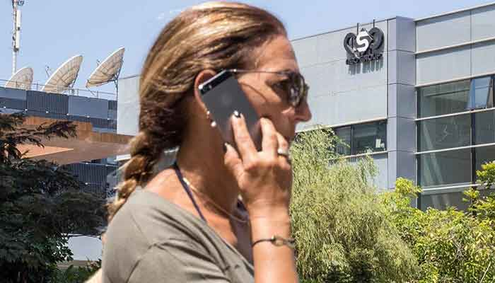 An Israeli woman uses her smartphone in front of the building housing the Israeli NSO group, on August 28, 2016, in Herzliya, near Tel Aviv. — AFP