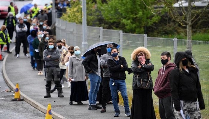 Members of the public queue to receive a Covid-19 vaccine at a temporary clinic at Essa Academy, a school in Bolton, north-west England. Photo: AFP