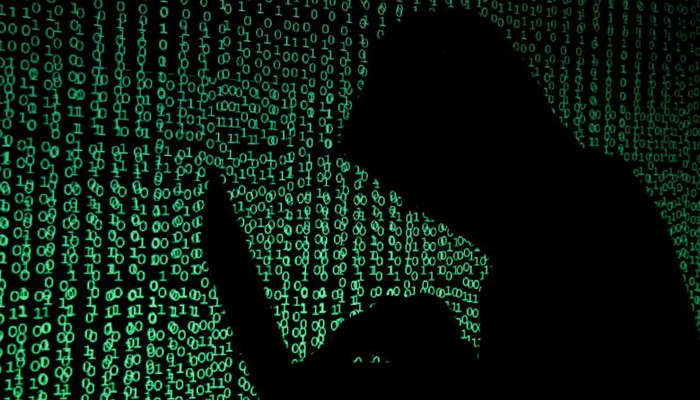 A hooded man holds a laptop computer as cyber code is projected on him in this illustration picture taken on May 13, 2017. — Reuters/File