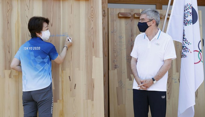 Tokyo 2020 President Seiko Hashimoto signs her autograph on a mural set up to wish for a truce in warring areas of the world during the Olympic Games while IOC President Thomas Bach looks on, at the athletes village in Tokyo, Japan July 19, 2021. Photo: Kyodo/via Reuters