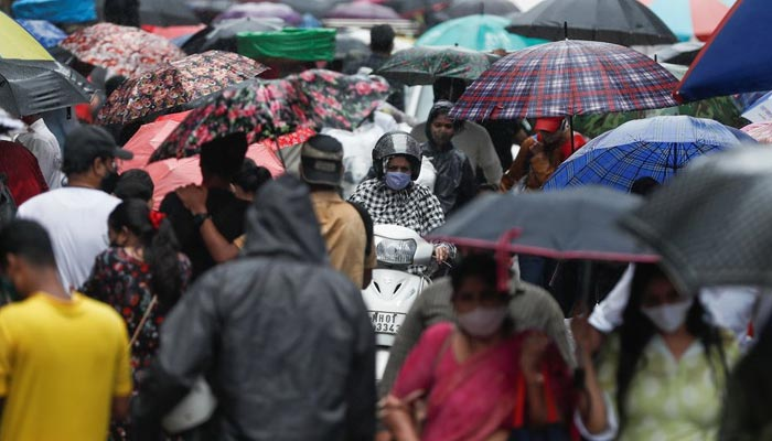 A woman rides a scooter through a crowded market on a rainy day amidst the spread of the coronavirus disease (COVID-19) in Mumbai, India, on July 14, 2021. — Reuters/File
