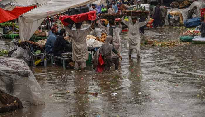Vendors carry wares on their heads to shelter from the rains amid a waterlogged street along a market area during heavy monsoon rains in Lahore on July 20, 2021. — AFP/Arif Ali