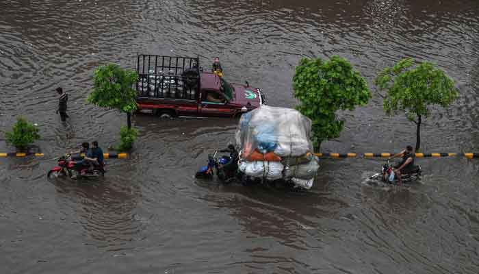 Commuters make their way through a flooded street after heavy monsoon rains in Lahore on July 20, 2021. — AFP/Arif Ali