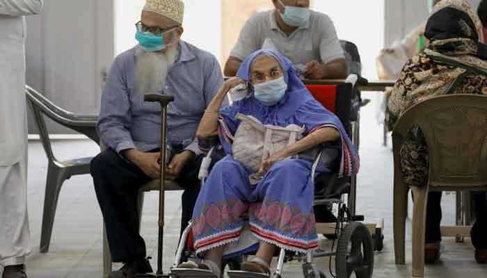Residents wait for their coronavirus disease (COVID-19) vaccine doses, at a vaccination center in Karachi, Pakistan, April 2, 2021. — Reuters/Akhtar Soomro