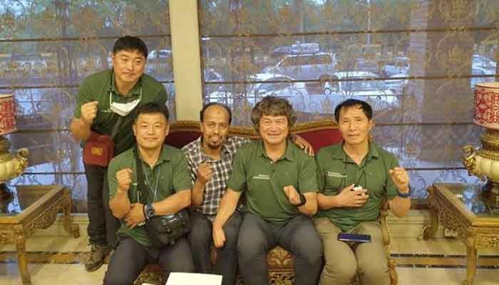South Korean climber Kim Hong-Bin (2nd R) and his team pose with a member of Alpine Club of Pakistan at the airport in Islamabad, Pakistan, June 16, 2021. — Karrar Haidri/Alpine Club of Pakistan/Handout via Reuters
