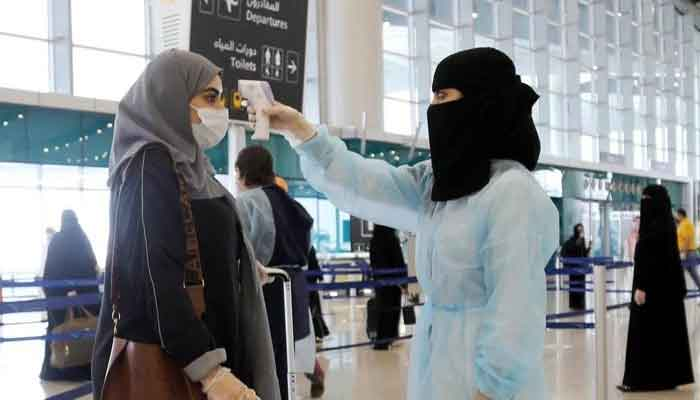 A traveller has her temperature checked at Riyadh International Airport. — Reuters/File