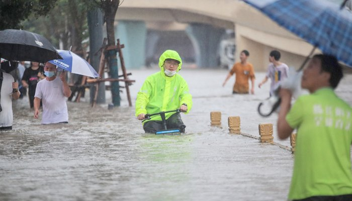 This photo taken on July 20, 2021 shows a man riding a bicycle through flood waters along a street following heavy rains in Zhengzhou in China´s central Henan province. — AFP/File