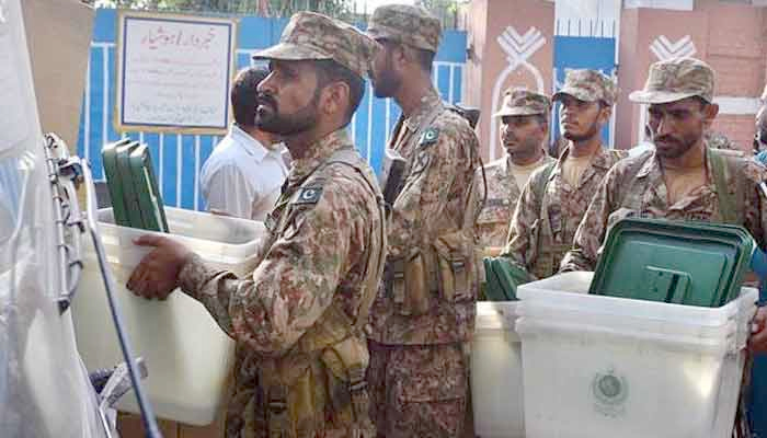 Pakistan Army troops assist in the election process by carrying the ballot boxes. — File photo