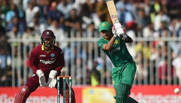 A file photo of Babar Azam hitting a shot as a West Indies wicketkeeper looks on.