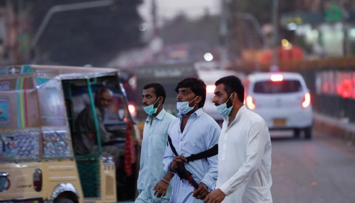 Three people, without wearing their masks properly, could be seen walking on the streets of Karachi. Reuters.
