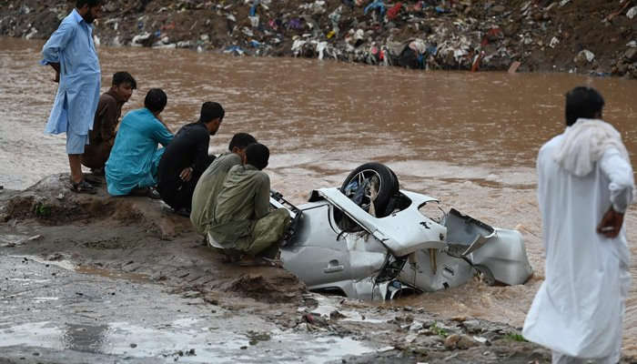 Residents gather as they look at a damaged car submerged in flood waters after heavy monsoon rains in Islamabad on July 28, 2021. — AFP