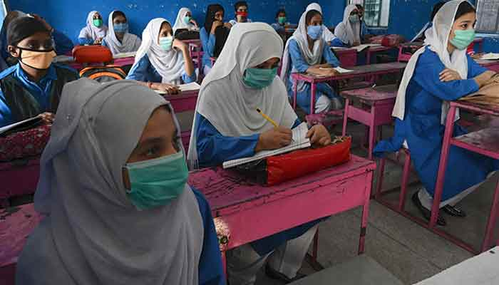 Schoolgirls wearing face masks sitting in a classroom. Source: AFP