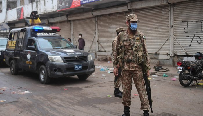 Army personnel and policemen arrive at a market to enforce an evening lockdown imposed amid rising COVID-19 coronavirus cases in Karachi on July 28, 2021. — AFP/File