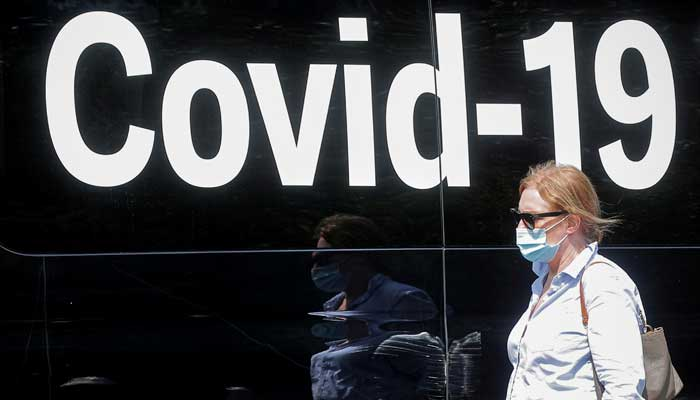 A woman wearing a mask passes by a coronavirus disease mobile testing van, as cases of the infectious Delta variant of COVID-19 continue to rise, in Washington Square Park in New York City, U.S., July 22, 2021. -Reuters