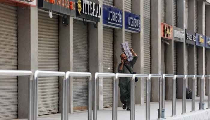 A man walks past a closed market during a partial lockdown after Sindh provincial government decided to shut markets, restaurants, public beaches and discouraged large gatherings to curb the outbreak of the coronavirus disease (COVID-19), in Karachi, Pakistan, July 30, 2021. — Reuters