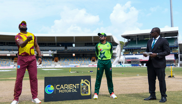 Kieron Pollard (L) of West Indies tosses the coin as Babar Azam (C) and match referee Sir Richie Richardson (R) look on during the 1st T20I between West Indies and Pakistan at Kensington Oval, Bridgetown, Barbados, on July 28, 2021. — AFP/File
