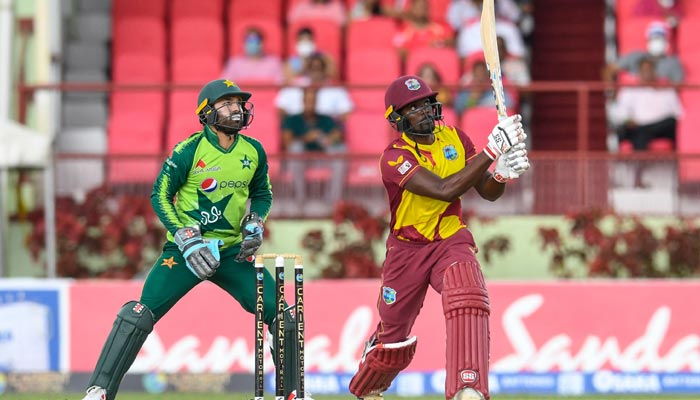 Andre Fletcher (R) of West Indies hits 6 and Mohammad Rizwan (L) of Pakistan watches during the 3rd T20I match between West Indies and Pakistan at Guyana National Stadium in Providence, Guyana on August 1, 2021. — AFP