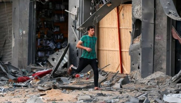 A Palestinian man runs for cover during an Israeli air attack near the site of a destroyed tower building in Gaza City. Photo: Reuters