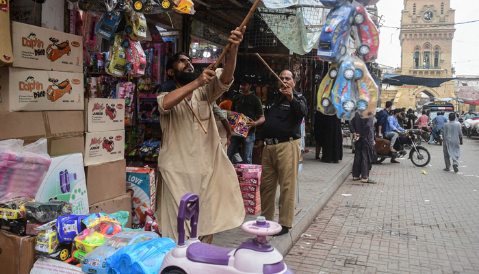 A policeman orders shopkeepers to close their shops after authorities imposed evening lockdowns amidst rising COVID-19 coronavirus cases in Karachi on July 26, 2021 — AFP/File