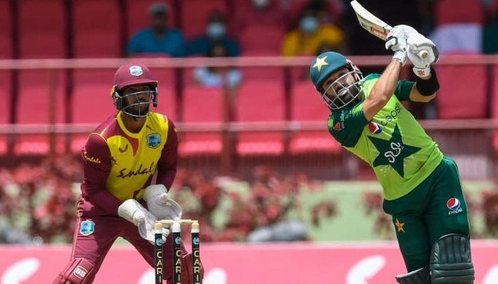 Pakistan batsman Mohammad Rizwan smashes the ball for a six as the West Indies wicketkeeper looks on. Photo: AFP