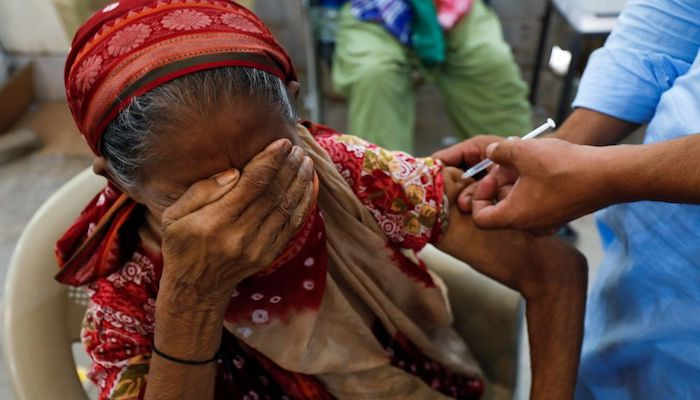 Basanti, 71, reacts as she receives a dose of the coronavirus disease (COVID-19) vaccine at a vaccination center in Karachi, Pakistan June 9, 2021. Photo: Reuters