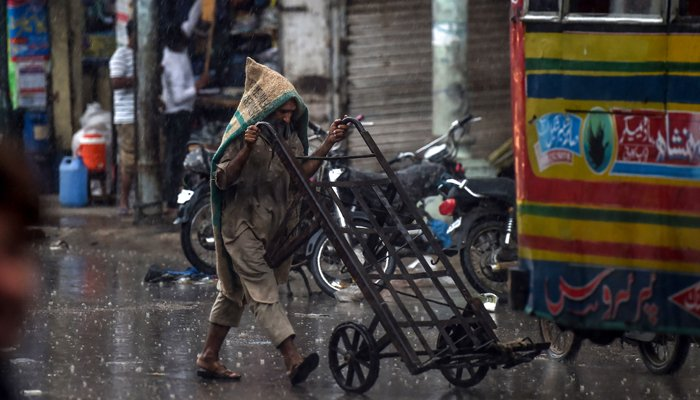 A labourer covers himself as he pushes a cart on a street under the rain in Karachi on August 6, 2020. — AFP/Asif Hassan