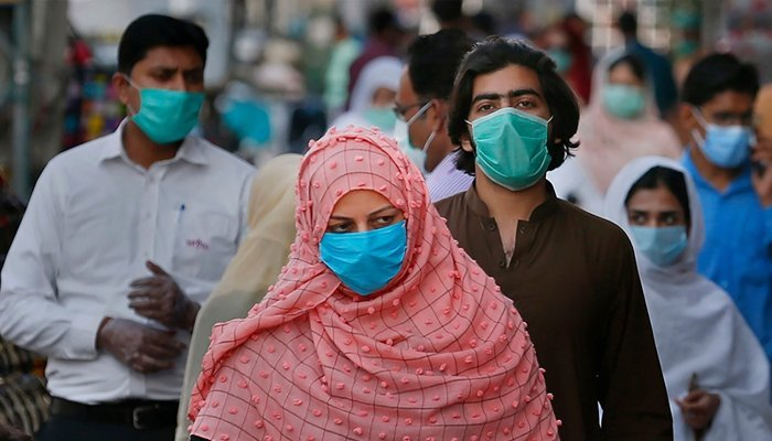 Masked people walk in a market somewhere in Pakistan. Photo: AFP