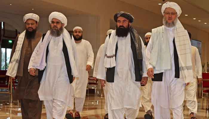 Head of the Taliban delegation Abdul Salam Hanafi (R), walks down a hotel lobby during the talks in Qatars capital Doha on August 12, 2021. — Photo by Karim Jaafar/AFP