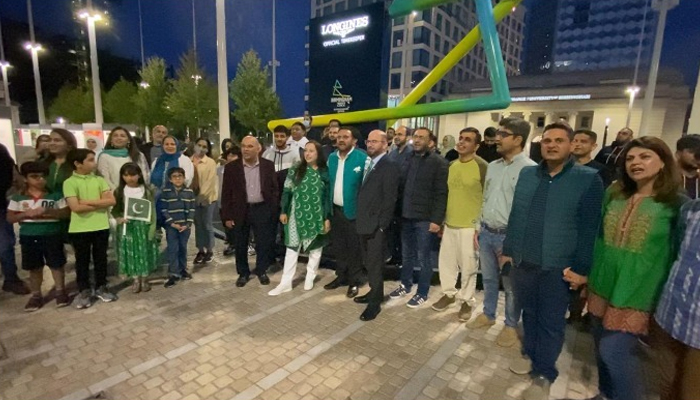 People standing outsidethe Library of Birmingham which was lit up green and white on the occasion of Pakistan's 75th Independence Day, on August 14, 2021, in Birmingham, UK. — Photo by authors