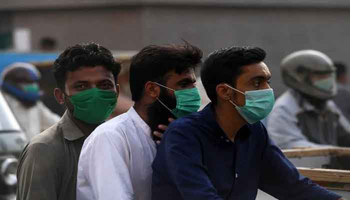 Three men on board a motorcycle are seen wearing surgical masks in this AFP file photo from Pakistan.