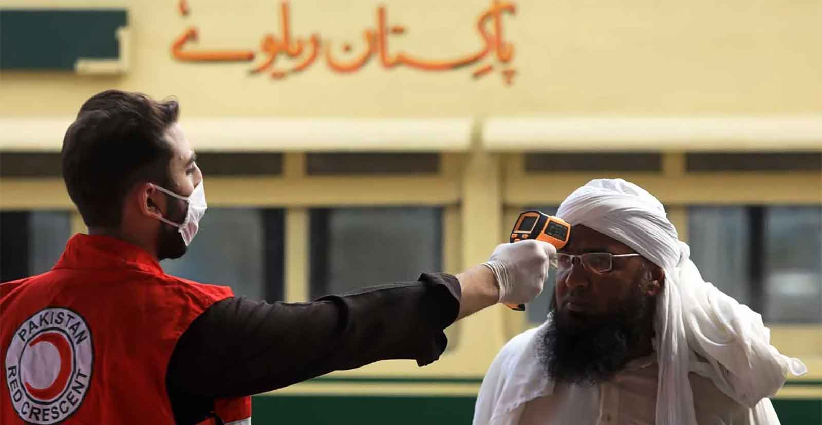 A Pakistan Red Crescent worker checks a man for his temperature using a thermal gun. Photo: AFP