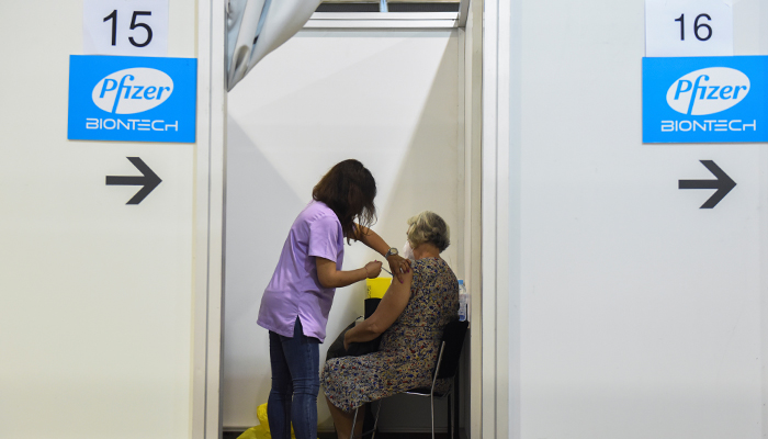 A healthcare worker administers the third dose of Pfizers coronavirus disease (COVID-19) vaccine to a woman at Belgrade Fair vaccination centre in Belgrade, Serbia, August 25, 2021. — Reuters